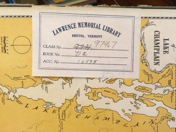 end paper of a book showing lake Champlain with a checkout card stuck on top of it